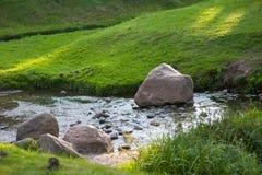 石头在河干涉水流程,由河的草坪 免版税库存图片