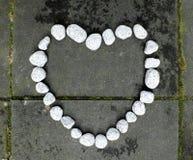 石头般的心由小白色石头做成在黑暗的石背景 免版税库存图片