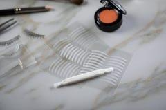 眼影调色板、刷子、假鞭子、镊子和人为眼皮折痕双重磁带眼睛构成的在大理石秀丽书桌上 免版税图库摄影