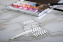 眼影调色板、刷子和人为眼皮折痕双重磁带眼睛构成的在大理石秀丽 库存照片