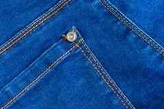 真正的蓝色牛仔裤牛仔布织品背景纹理 有橙黄缝和铆钉的空的后面口袋 免版税库存照片