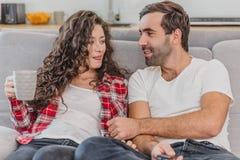 真的爱 快乐的浪漫夫妇坐在一舒适屋子和微笑的长沙发 图库摄影
