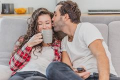 真的爱 快乐的浪漫夫妇坐在一舒适屋子和微笑的长沙发 免版税库存照片