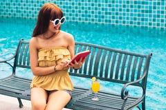 看她的手机,智能手机ot片剂的一个退出的年轻亚洲人女孩的画象坐椅子 免版税库存图片