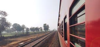 看在印度铁路特级列车的窗口外面以绿色农场土地为目的 库存照片