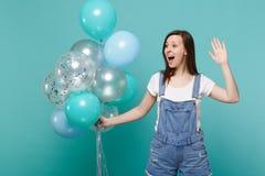 看在旁边挥动的问候用手的惊奇的女孩作为通知庆祝的某人拿着五颜六色的气球 库存图片