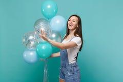 看在旁边,挥动的问候用手作为通知的微笑的妇女庆祝的某人拿着五颜六色的气球 库存图片
