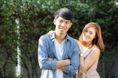 看每其他眼睛和微笑与愉快,年轻亚裔人和妇女联系的美好的画象夫妇与爱约会 免版税库存图片