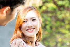 看每其他眼睛和微笑与愉快,年轻亚裔人和妇女联系的美好的画象夫妇与爱约会 免版税库存照片