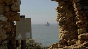看法通过古老墙壁,在停车处的海罐车遗骸  免版税图库摄影