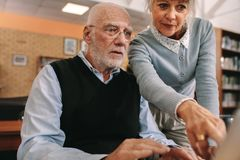 看显示器的老人和妇女 免版税库存照片