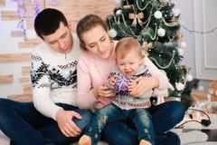 看照相机的友好的家庭画象在圣诞节晚上 图库摄影