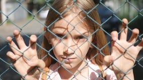 看照相机的被抛弃的,不快乐的离群女孩孩子孤儿的哀伤的沮丧的孩子 免版税库存图片