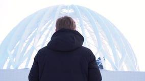 看马戏圆顶,Ekaterinburg,俄罗斯的一个人的背面图 后面观点的在黑夹克的一个男性在前面 库存照片