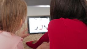 看鞋类的母亲和小女儿,当购物在网上在数字片剂时 网上购物的概念 股票录像