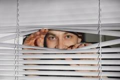 看通过威尼斯式窗口的好奇人 免版税库存照片