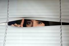 看通过威尼斯式窗口的好奇妇女 图库摄影