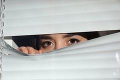看通过威尼斯式窗口的好奇妇女 免版税库存照片