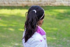的女孩看某事的后面观点 库存图片