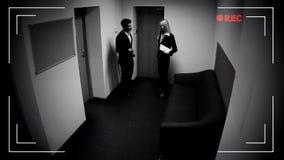 的男性和谈女性的同事办公室走廊,CCTV照相机作用,英尺长度 免版税库存照片