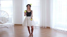 玩杂耍与网球的年轻女人芭蕾舞女演员走直接 股票视频