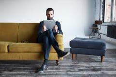 现代技术使用 有胡子的周道的商人看数字片剂,当坐沙发在办公室时 库存图片