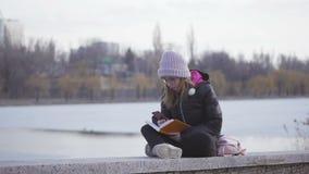 玻璃和一个桃红色帽子的一少女由河坐春天下午采取与一支笔的笔记在笔记本 影视素材