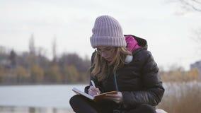 玻璃和一个桃红色帽子的一少女由河坐春天下午采取与一支笔的笔记在笔记本 股票录像