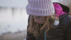 玻璃和一个桃红色帽子的一少女由河坐春天下午采取与一支笔的笔记在笔记本 股票视频