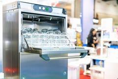 玻璃板的关闭和茶杯或者翻转者在篮子在自动洗碗机机器工业的 免版税库存照片
