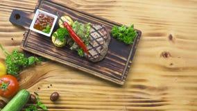 烤肉牛排构成顶视图 烤牛排用炽热胡椒、草本、玉米和西红柿酱在木板 影视素材
