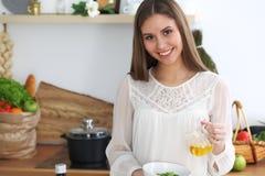 烹调在厨房里的年轻愉快的妇女 健康膳食、生活方式和烹饪概念 早晨好从新鲜开始 库存照片