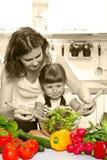 烹调晚餐的母亲和女儿在厨房里 免版税库存照片