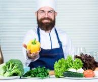烹调甜椒的厨师 烹调在厨房里的男服围裙 烹调健康食谱胡椒菜的人 烹调  库存图片