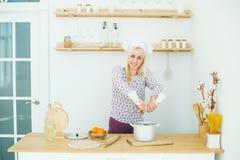 烹调食物的年轻白种人妇女在厨房里 库存图片