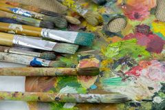 爱好、工作、艺术和生活在不同颜色在一个调色板有的刷子 有刷子特写镜头的艺术家调色板 免版税库存图片