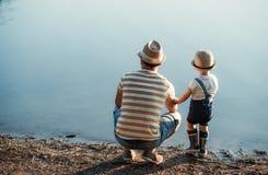 父亲一个背面图有小小孩儿子消费时间户外的由湖 免版税库存照片