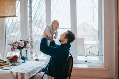 父亲在他的胳膊拿着他微小的儿子坐椅子在一个大窗口旁边在厨房里 免版税库存图片