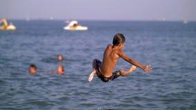 父亲在天空中投掷他的儿子入跃迁的海,男孩在海上 免版税库存照片