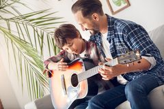 父亲和一点儿子在家坐沙发爸爸弹吉他的教学男孩快乐 库存图片