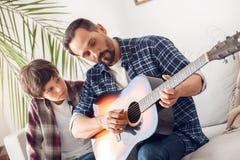 父亲和一点儿子在家坐看铭记爸爸的沙发男孩弹吉他 免版税图库摄影