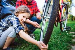父亲和女儿自行车的定象问题室外在夏天 免版税库存图片
