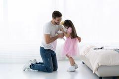 父亲祝贺女儿与开心3月8日 女儿和父亲微笑 美丽的女儿的大熊 免版税图库摄影