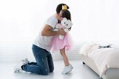 父亲祝贺女儿与开心3月8日 女儿和父亲微笑 美丽的女儿的大熊 库存照片
