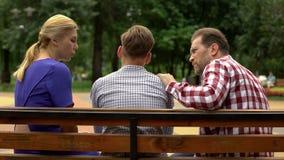 父母谈话与长凳的儿子在公园,支持的青少年在麻烦的时候 免版税图库摄影