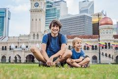 爸爸和儿子独立报广场和苏丹阿卜杜勒萨玛德大厦背景的  旅行与儿童概念 免版税库存照片