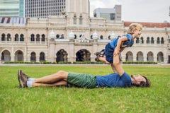 爸爸和儿子独立报广场和苏丹阿卜杜勒萨玛德大厦背景的  旅行与儿童概念 图库摄影