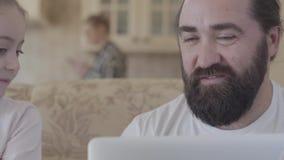 爸爸接近的画象有逗人喜爱的谈论女儿和的膝上型计算机的在客厅坐长沙发和 股票录像