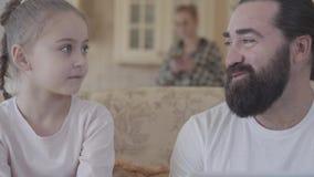 爸爸画象有逗人喜爱的在客厅坐长沙发和谈论事的女儿和膝上型计算机的滑稽 股票视频