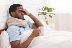 病的非裔美国人的人在床上的喝热的医治用的茶 库存图片